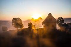 dekorativt litet tr?hus p? solnedg?ngbakgrunden arkivfoton