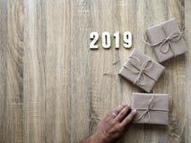 Dekorativt lyckligt nytt år 2019 med gåvaasken på trä arkivfoton