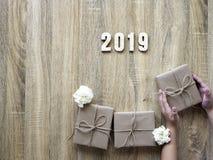 Dekorativt lyckligt nytt år 2019 med gåvaasken på trä arkivbild