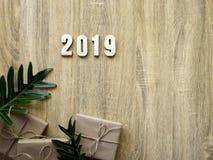 Dekorativt lyckligt nytt år 2019 med gåvaasken på trä arkivfoto