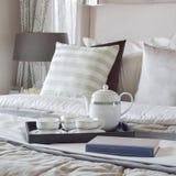 Dekorativt magasin med boken och teservis på sängen i modernt sovrum arkivbilder