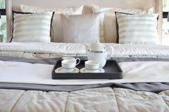 Dekorativt magasin med det svarta magasinet av teservisen på sängen i modern sovruminre royaltyfri bild