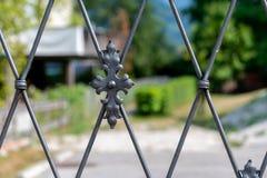 Dekorativt metallstaket, som det gjorda suddig huset och trädgården är synligt bak royaltyfri foto