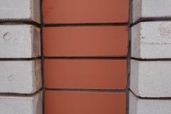 Dekorativt murverk som göras av vita och orange tegelstenar Arkivbilder