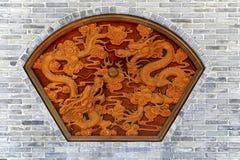 Dekorativt snida av drakar på väggen Arkivfoto