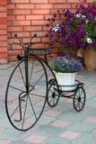 Dekorativt stativ för retro cykel för blommor mot en tegelstenvägg Arkivbild