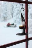 Dekorativt stearinljus på fönster och snowmobile Arkivbilder