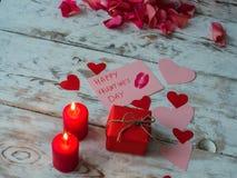 Dekoren för St-valentin` s på träbakgrund, röda stearinljus med den röda gåvan och hjärtor från hantverket skyler över brister Fotografering för Bildbyråer