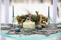 Dekorera bröllopstårtan med vinterblommor och stearinljus arkivfoto