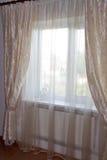 Dekorera fönster - kräm hänger upp gardiner i sovrummet Arkivfoto