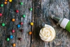 Dekorera läckra hemlagade muffin med smörkräm royaltyfri fotografi