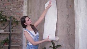 Dekorera lägenheten och folk, väljer den härliga flickan tapeten av prövkopior nära den tomma väggen under renovering i rum