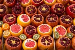 Dekorerad apelsin, granatäpple och kiwi på marknadshyllan royaltyfri fotografi