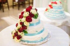 Dekorerad bröllopstårta med rosor för röda och vita blommor på vit bakgrund royaltyfria bilder