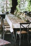 Dekorerad elegant brölloptabell för matställe med blom- vita buketter, ljusstakar och exponeringsglas för en vitbordduk och royaltyfria foton