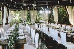 Dekorerad elegant träbrölloptabell för banketten som är utomhus- i trädgårds- gazebo med lampan, i stilen av lantligt med eukalyp arkivbilder