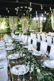 Dekorerad elegant träbrölloptabell i en gazebo med lantliga lampor med eukalyptuns och blommor, porslinplattor, exponeringsglas,  royaltyfria bilder