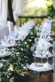 Dekorerad elegant träbrölloptabell i lantlig stil med eukalyptuns och blommor, porslinplattor och exponeringsglas arkivfoton