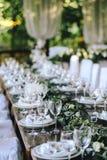 Dekorerad elegant träbrölloptabell i lantlig stil med eukalyptuns och blommor, porslinplattor och exponeringsglas royaltyfria foton