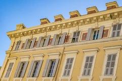 Dekorerad fasad av ett historiskt hus i Nice, Frankrike Du kan se de typiska fönstren och slutarna av ett medelhavs- c royaltyfri bild