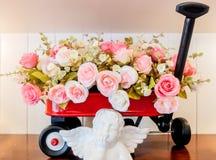 Dekorerad grupp av rosor i röd vagn med vita Angel Figure som är främst med utrymme över som matar in text Royaltyfri Foto
