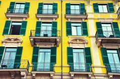 Dekorerad gul byggnadsfasad med gröna fönsterrullgardiner Arkivbild