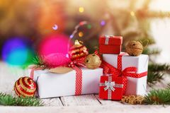 Dekorerad jul grupperar röda och vita gåvor och guld- klirrklockor på bakgrund letters amerikansk för färgexplosionen för kortet  Arkivbilder