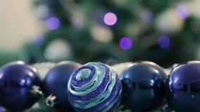 Dekorerad julgran med blåa ljus Julbollar i förgrunden Suddig bild av en julgran i bakgrunden stock video