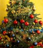 Dekorerad julgran med skriftliga lyckliga ferier i italienare Arkivfoton