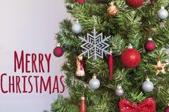 Dekorerad julgran med text för glad jul Arkivfoto