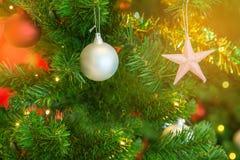 Dekorerad julgran och stjärna och bollar med dekorerade suddiga ljus Royaltyfri Foto