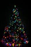 Dekorerad julgran som tänds upp med färgrika ljus Arkivbild