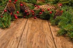 Dekorerad julgranträd och kotte på ett träbräde Fotografering för Bildbyråer