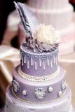 Dekorerad purpurfärgad bröllopstårta med blommor Royaltyfri Fotografi