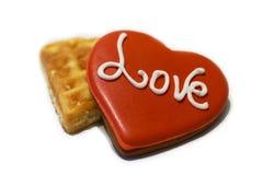 Dekorerad röd hjärta formade kakor med ordet FÖRÄLSKELSE på vit bakgrund, bästa sikt royaltyfri bild