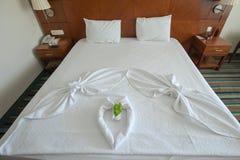 Dekorerad säng med handdukar och hjärta-formade räkningar arkivfoton
