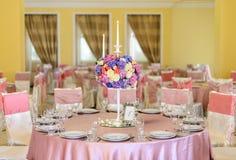 Dekorerad tabell med härliga blommor i den eleganta restaurangen för det perfekta bröllopet Royaltyfri Bild