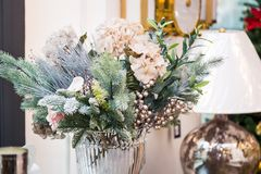 Dekorerad vas med härliga vit blomma- och julträdfilialer, ljus inre med garneringar på bakgrunden royaltyfri foto