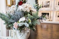 Dekorerad vas med härliga vit blomma- och julträdfilialer, ljus inre med garneringar på bakgrunden arkivfoton