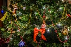 Dekorerade den konstgjorda julgranen för jul med en girland och julleksaker Arkivfoton