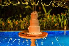 Dekorerade den tre rad varvade bröllopstårtan med vit marsipanisläggning med orkidér på en tabell nära pölen arkivbild