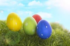Dekorerade easter ägg i gräs på himmelbakgrund Arkivfoton