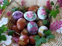 Dekorerade easter ägg i vävd korg Arkivbilder