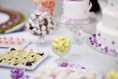 Dekorerade färgrika godisar på en vit tabell Royaltyfri Foto