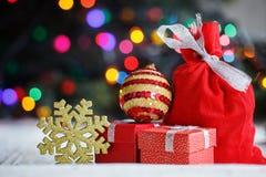 Dekorerade julgåvor och guld- snöflinga, påse santa på färgrika ljus letters amerikansk för färgexplosionen för kortet 3d ferie f Royaltyfri Bild