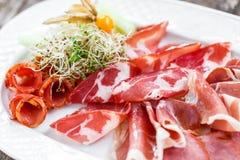 Dekorerade plattan för kallt kött för Antipastouppläggningsfatet med prosciuttoen, skivor skinka, salami, med physalisen och skiv Royaltyfri Foto