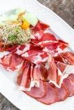 Dekorerade plattan för kallt kött för Antipastouppläggningsfatet med prosciuttoen, skivor skinka, salami, med physalisen och skiv Arkivbilder
