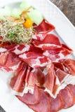 Dekorerade plattan för kallt kött för Antipastouppläggningsfatet med prosciuttoen, skivor skinka, salami, med physalisen och skiv Royaltyfria Foton