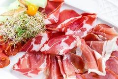Dekorerade plattan för kallt kött för Antipastouppläggningsfatet med prosciuttoen, skivor skinka, salami, med physalisen och skiv Arkivfoton