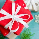 Dekorerade röda askar för jul av gåvor festively på en turkos Royaltyfria Bilder
